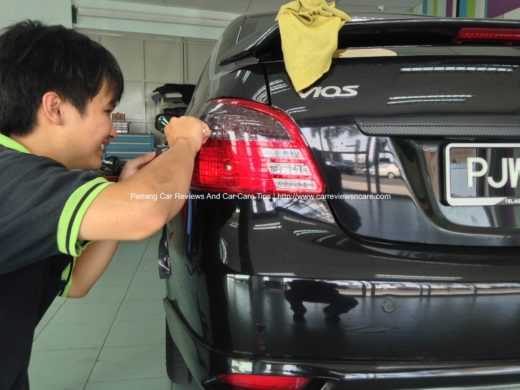 happy worker cutting the excess tint film on the Toyota Vios tail lamp