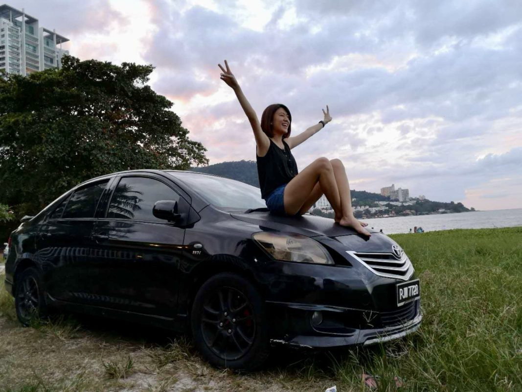 Jenny Wong (babe) sitting on car hood to enjoy sea breeze at Tanjung Bungah Beach